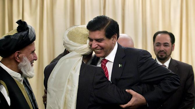 Pakistan's Prime Minister Raja Pervaiz Ashraf, center, hugs a member of the delegation of Afghanistan's High Peace Council, prior to their meeting in Islamabad, Pakistan, Monday, Nov. 12, 2012. The council's head Salahuddin Rabbani stands at right. (AP Photo/Anjum Naveed)