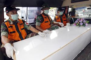 Indonesian military personnel sit with a coffin containing…