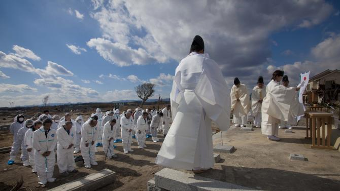 FILE - In this Feb. 19, 2012 file photo, Japanese evacuees from the towns inside the nuclear exclusion zone bow as Shinto priests hold a memorial ceremony in the abandoned and irradiated town of Namie in Japan's Fukushima prefecture when a group of former residents returned to the area for the day to hold the ceremony at the site of the ancient Kusano shrine that was destroyed by the March 11, 2011 tsunami. Experts and the government say there have been no visible health effects from the radioactive contamination from Fukushima Dai-ichi so far. But they also warn that even low-dose radiation carries some risk of cancer and other diseases, and exposure should be avoided as much as possible, especially the intake of contaminated food and water. Such risks are several times higher for children and even higher for fetuses, and may not appear for years. Okinawa has welcomed the people from Fukushima and other northeastern prefectures (states) affected by the March 11, 2011, earthquake and tsunami that set off the nuclear disaster. (AP Photo/David Guttenfelder, File)