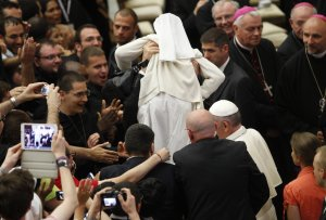 A Vatican security officer holds up a nun as Pope Francis …