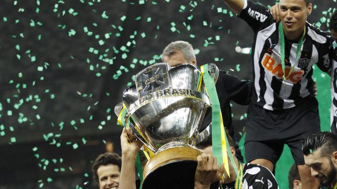 Silva of Atletico Mineiro celebrates with the Copa do Brasil trophy with teammates after winning the final soccer match against Cruzeiro at Mineirao stadium in Belo Horizonte