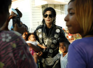 Michael Jackson impersonator Carlo Riley from Denver, poses with three children near Jackson's boyhood home during celebrations marking what would have been Jackson's 54th birthday Wednesday, Aug. 29, 2012, in Gary, Ind. (AP Photo/Sitthixay Ditthavong)