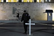 A Greek policeman removes a cross reading 'Dignity', that was placed by protesters in front of the parliament in Athens on April 8. With recession looming in debt-struck Europe, governments face growing pleas to move away from all-out austerity and inject growth policies as leaders struggle to revive their economies.