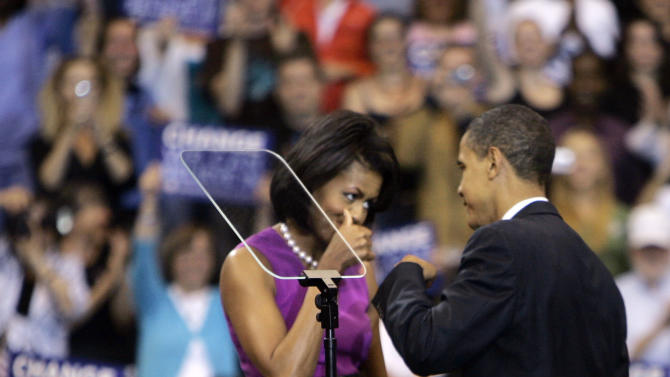 FILE - This June 3, 2008, file photo shows then Democratic presidential candidate Sen. Barack Obama fist bump with his wife Michelle, before speaking at a primary night rally in St. Paul, Minn.  Though the knuckle-tapping action has been around for years, fist bump's place in popular culture was cemented by President Obama and First Lady Michelle Obama when they did it at the convention, and now has earned a spot in the Merriam-Webster Collegiate Dictionary. (AP Photo/Morry Gash, File)