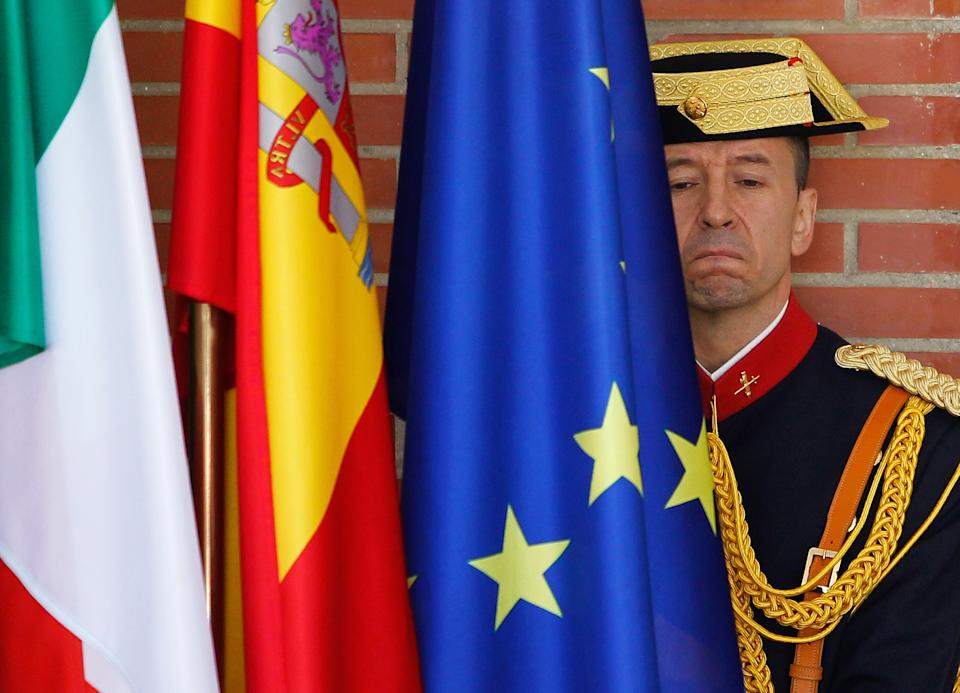 A police officer stands guard beside the flags of the European Community, Spain and Italy during the meeting between Italy's Prime Minister Mario Monti, unseen, and Spain's Prime Minister Mariano Rajoy, unseen, at the Moncloa Palace in Madrid, Spain, Thursday, Aug. 2, 2012. (AP Photo/Andres Kudacki)