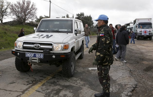 A Filipino United Nations peacekeeper stands next to a U.N. vehicle before it crosses from Israel into Syria at the Kuneitra border crossing on the Golan Heights March 5, 2013. Syrian rebels have seized a convoy of U.N. peacekeepers near the Golan Heights and say they will hold them captive until President Bashar al-Assad's forces pull back from a rebel-held village which has seen heavy recent fighting. Israel captured the Golan Heights in the 1967 Middle East war and annexed it in 1981 in a move not recognized internationally. Picture taken March 5, 2013. REUTERS/Baz Ratner (POLITICS TRANSPORT)