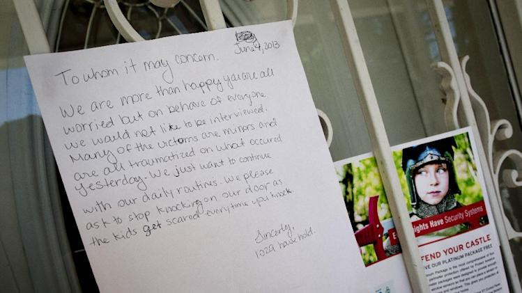 A note is posted Tuesday, June 4, 2013, on the home of a 10-year-old Brooklyn boy who police say on Monday picked up a gun dropped by a would-be robber dressed as a delivery man and fired a shot, in New York. No injuries were reported. (AP Photo/John Minchillo)