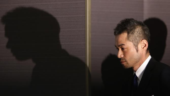 Japan's outfielder Ichiro Suzuki walks into a news conference to announce an agreement on a one-year contract with the Miami Marlins in Tokyo
