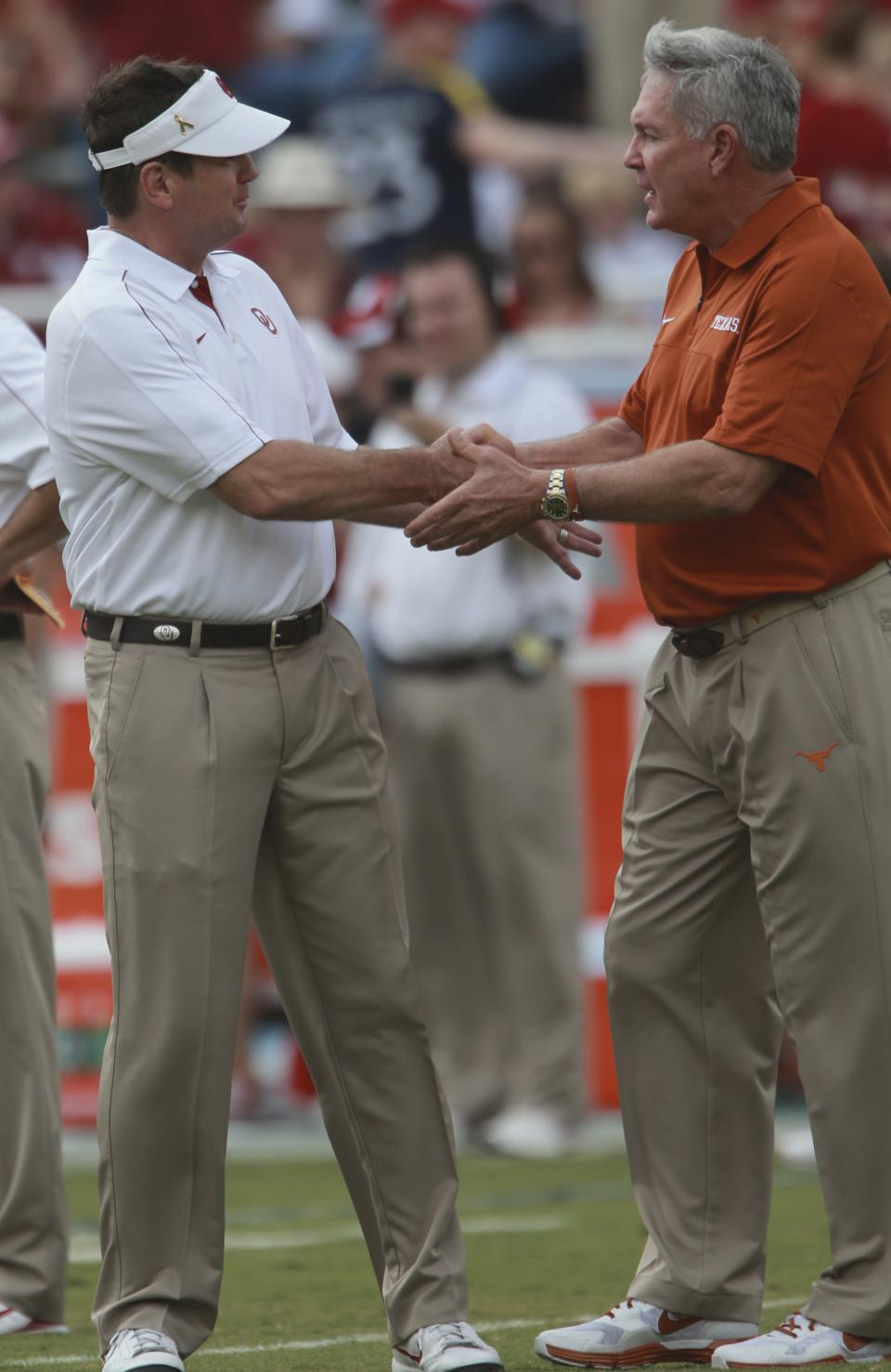 Texas head coach Mack Brown, right, and Oklahoma head coach Bob Stoops chat before their NCAA college football game at the Cotton Bowl Saturday, Oct. 13, 2012, in Dallas. (AP Photo/Michael Mulvey)