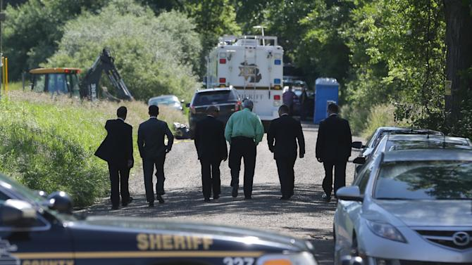 Law enforcement officials walk back to the search area after Robert Foley, special agent in charge of the FBI's Detroit division, addressed the media in Oakland Township, Mich., Wednesday, June 19, 2013 and announced the FBI was ending the search operations for the remains of Teamsters union president Jimmy Hoffa who disappeared from a Detroit-area restaurant in 1975. (AP Photo/Carlos Osorio)a