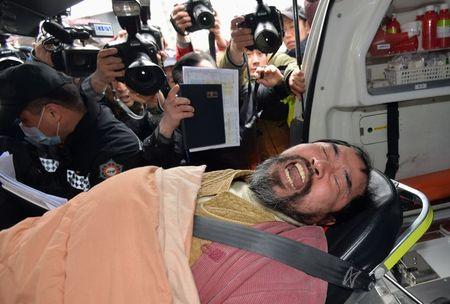 Kim Ki-jong who attacked the U.S. ambassador to South Korea Mark Lippert at a public forum, is carried on a stretcher off an ambulance as he arrives at a hospital in Seoul