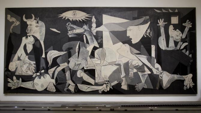 """FILE - This Feb. 21, 2012 file photo shows Pablo Picasso's """"Guernica"""" painting displayed at the Reina Sofia Museum in Madrid. The museum was one of a number of places visited by Raf Casert on a father-son trip to the city with his teenage son. (AP Photo/Paul White, file)"""
