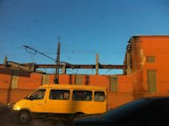In this photo taken with a mobile phone camera, a minivan passes a zinc factory building with about 600 square meters (6000 square feet) of a roof collapsed in Chelyabinsk on Friday, Feb. 15, 2013. A meteor streaked across the sky of Russias Ural Mountains on Friday morning, causing sharp explosions and reportedly injuring around 100 people, including many hurt by broken glass. (AP Photo/Valentin Kazakov)