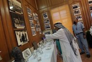"A visitor looks at memorabilia displayed during a private exhibition in Baghdad. ""This exhibition gives visitors glimpses of an important phase in the modern history of Iraq that lasted for almost 40 years,"" said Adil al-Ardawi, an Iraqi historian"