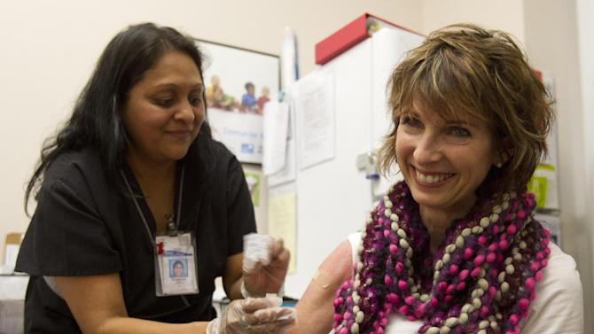 Diane Ewell, of Phoenix, right, gets a flu shot from nurse Bhagwati Bhakta at Mollen Immunization Clinics in Scottsdale, Ariz. Thursday, Jan. 10, 2013. Arizona health officials say flu activity is widespread in the state this week with influenza reported in 14 of its 15 counties. (AP Photo/The Arizona Republic, Cheryl Evans)  MARICOPA COUNTY OUT; MAGS OUT; NO SALES