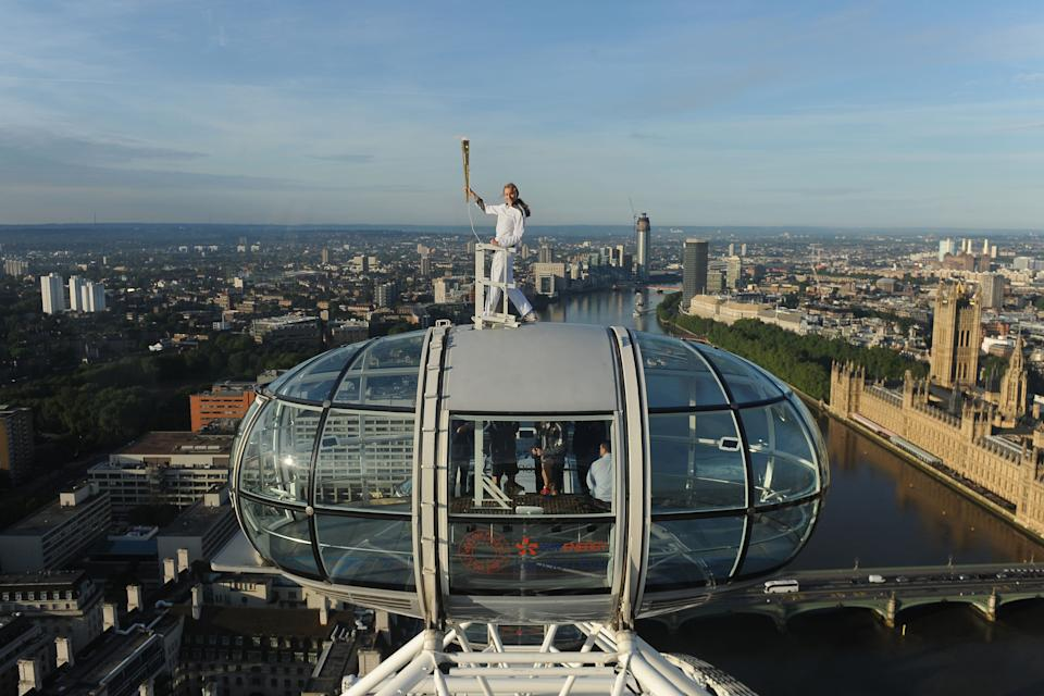 In this photo provided by LOCOG, Amelia Hempleman-Adams poses with the Olympic Flame on top of a London Eye pod on the Torch Relay leg through London, Sunday July 22, 2012. Opening Ceremonies for the 2012 London Olympics will be held Friday July 27. (AP Photo/LOCOG, Lewis Whyld)