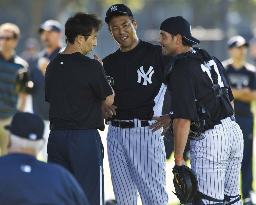 New York Yankees catcher Cervelli talks with pitcher Kuroda and interpreter Nimura in the bullpen during the first formal workout for pitchers and catchers at the team's spring training complex in Tampa