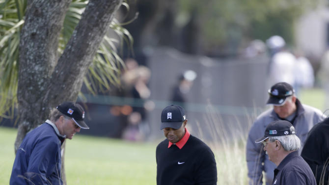 Tiger Woods, center, looks for his ball with others after having teed off on the sixth and lost his ball somewhere on the fourth fairway during the final round of the Honda Classic golf tournament on Sunday, March 3, 2013 in Palm Beach Gardens, Fla. (AP Photo/Wilfredo Lee)