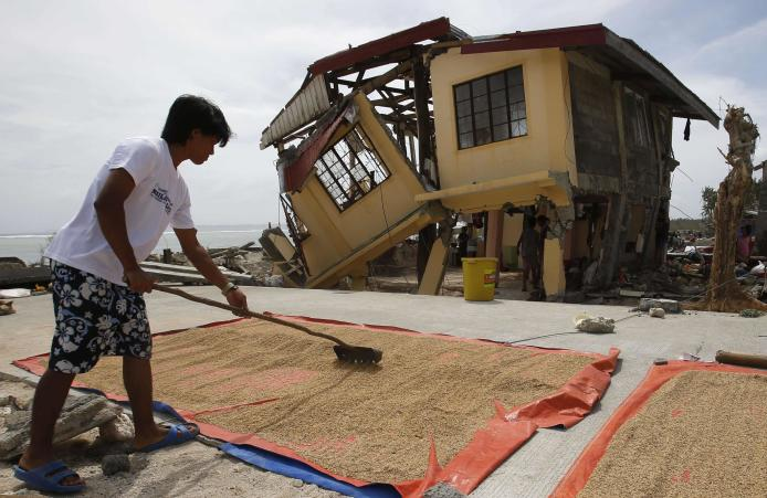 A man dries rice bran in front of his house damaged by super Typhoon Haiyan in Hernani, Samar, in central Philippines