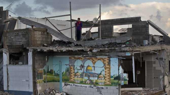 A Palestinian boy looks from the rooftop of a destroyed house in Gaza City, Sunday, Nov. 25, 2012. A leading Islamic cleric in the Gaza Strip has ruled it a sin to violate the recent cease-fire between Israel and the Hamas militant group that governs the Palestinian territory according a religious legitimacy to the truce and giving the Gaza government strong backing to enforce it. (AP Photo/Bernat Armangue)