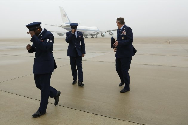 U.S. Air Force Colonel Minihan and fellow officers hold onto their hats after saluting President Obama upon his departure aboard Air Force One in foggy conditions at Joint Base Andrews, Maryland