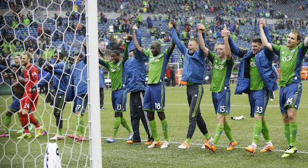 Seattle Sounders players and other team personnel celebrate after the Sounders beat Sporting Kansas City 1-0 in an MLS soccer match, Saturday, March 8, 2014, in Seattle