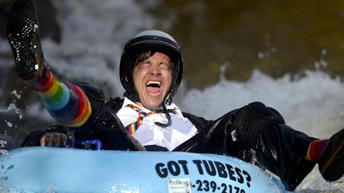Co-Founder Jeff Kagan laughs after crashing through rough water during the 7th Annual Tube to Work Day in Boulder, Colo., Tuesday, July 15, 2014. (AP Photo/Boulder Daily Camera, Mark Leffingwell)