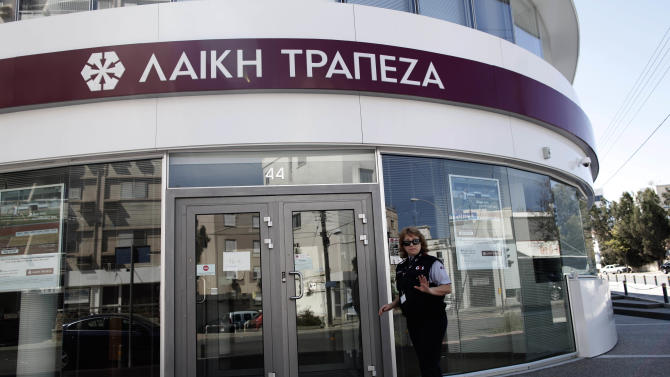 A private security guard gestures outside a Laiki bank branch in Nicosia, Cyprus, Thursday, March 28, 2013. Bank branches across the country were being replenished with cash, and are scheduled to open for six hours at noon (1000 GMT). Systems were frozen pending the official noon opening, and guards from a private security firm were reinforcing police outside some ATMs and banks in the capital, Nicosia. (AP Photo/Petros Giannakouris)
