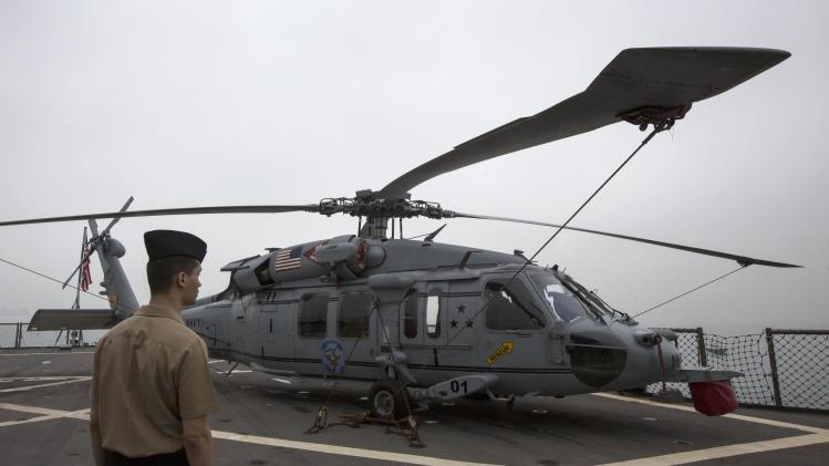 A U.S. Navy personnel walks past a Sikorsky SH-60 Seahawk military helicopter onboard the USS Blue Ridge (LCC-19) in Hong Kong waters