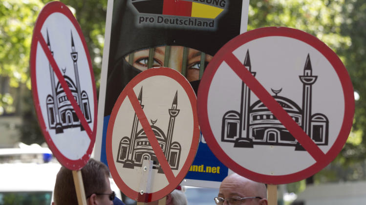"Demonstrators display signs, during a protest in front of a mosque in Berlin, Germany, Saturday, Aug. 18, 2012. A Berlin court had allowed the demonstration of the far-right group ' Pro Deutschland'  held under the slogan ""Islam does not belong in Germany — stop Islamization.""  (AP Photo/Gero Breloer)"