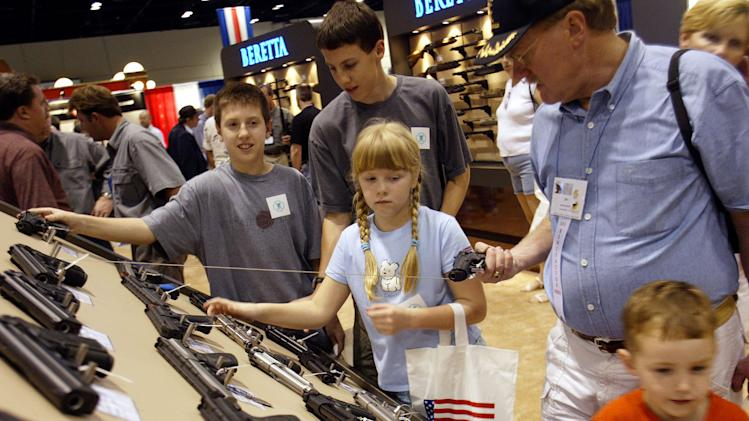 FAMILY CHECKS OUT GUNS AT NRA MEETING.