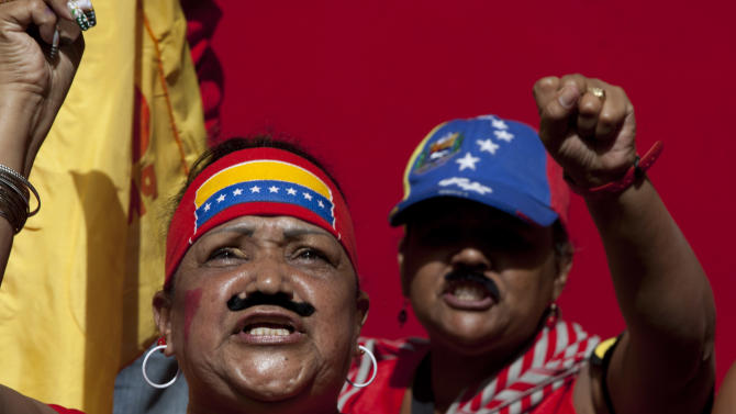 Supporters of Venezuela's President-elect Nicolas Maduro wear fake Maduro-style moustaches as they shout slogans outside the parliament building prior to his inauguration ceremony in Caracas, Venezuela, Friday, April 19, 2013. Opponents greeted officials' surprise announcement that they will accept an audit of the disputed vote that handed a narrow margin of victory to Maduro, the heir of late President Hugo Chavez.(AP Photo/Enric Marti)