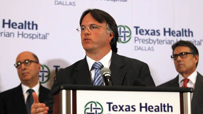 Lakey, Commissioner of Texas Department of State Health Services, speaks as Texas Governor Perry listens at a media conference at Texas Health Presbyterian Hospital in Dallas