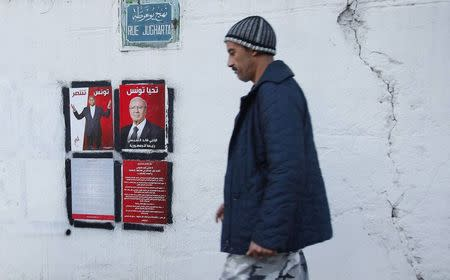 A man walks past election posters of presidential candidates in Tunis