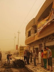 In the middle of a sand storm, Iraqis soliders inspect the debris following two car bombs in the western city of Ramadi, in the Anbar province