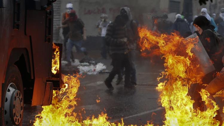 An anti-government protester stands with a shield near flames from molotov cocktails thrown at a water cannon by anti-government protester during riots in Caracas