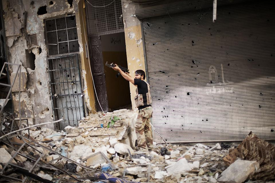 A Free Syrian Army fighter fires his weapon against Syrian Army positions in Karmal Jabl district, Aleppo, Syria, Sunday, Oct. 21, 2012. (AP Photo/ Manu Brabo)