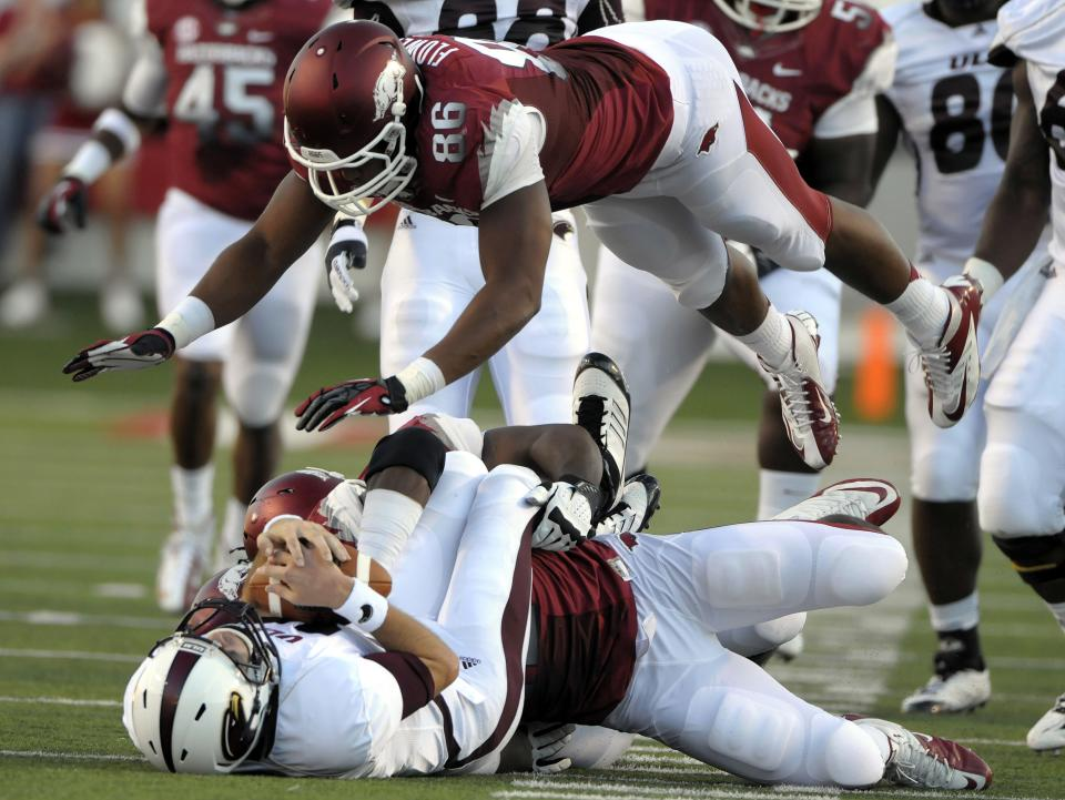Arkansas defensive end Chris Smith, bottom right, sacks Louisiana Monroe quarterback Kolton Browning for a 16-yard loss as Arkansas defensive end Trey Flowers (86) leaps over the pair during the first quarter of an NCAA college football game in Little Rock, Ark., Saturday, Sept. 8, 2012. (AP Photo/David Quinn)