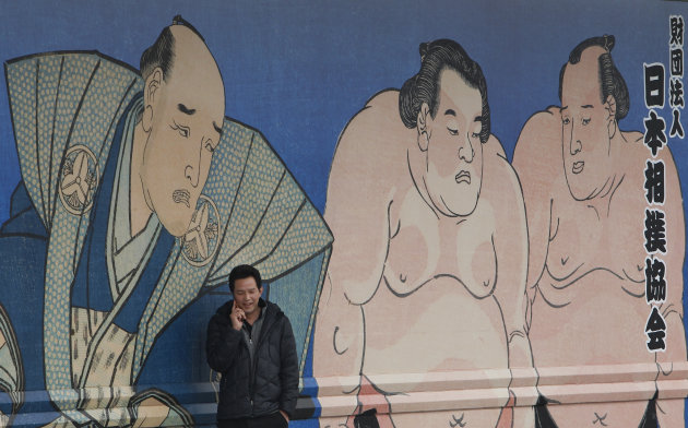 A media person talks on his cell phone outside Ryogoku Kokugikan sumo arena where the Japan Sumo Association is holding an emergency meeting in Tokyo Sunday, Feb. 6, 2011. In the meeting, the Japan Sumo Association decided to call off its Spring Grand Sumo Tournament scheduled for March, the first cancellation in 65 years, as the country&#39;s ancient sport grapples with a match-fixing scandal.