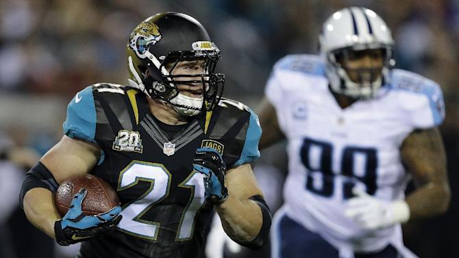 Jacksonville Jaguars running back Toby Gerhart (21) carries as Tennessee Titans defensive end Jurrell Casey (99) trails during the first quarter of an NFL football game Thursday, Dec. 18, 2014, in Jacksonville, Fla