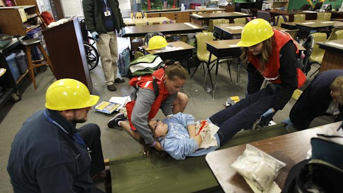 "Bella BeSerra, 9, role-plays the part of an injured student as she is lifted by P.E. teacher Kelly Miller, second from left, and health care assistant Piper Marker, right, onto a gurney as teacher Phil Schmitt looks on at left, during an earthquake drill at Twin Lakes Elementary School in Federal Way, Wash., Thursday, Oct. 18, 2012. Millions of people took part in the ""Great Shakeout"" earthquake drill across the country and elsewhere Thursday to practice and prepare for the possibility of real quakes in the future. (AP Photo/Ted S. Warren)"