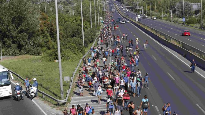 Migrants set off on foot for the border with Austria from Budapest