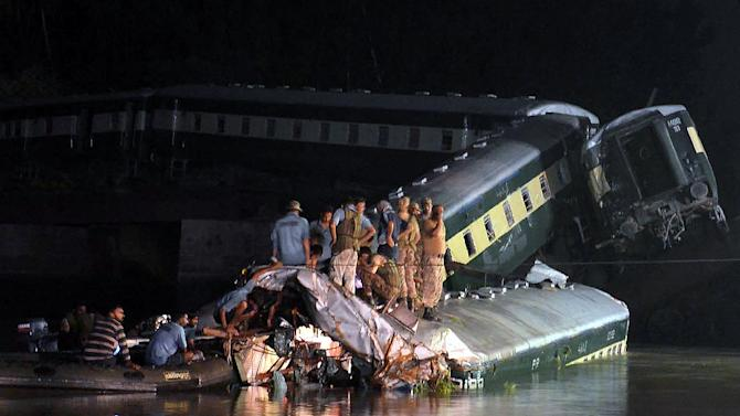 Rescue workers and troops inspect the wreckage of a train carrying soldiers and military hardware after it fell into a canal following the partial collapse of a bridge, in Wazirabad, Punjab province, on July 2, 2015