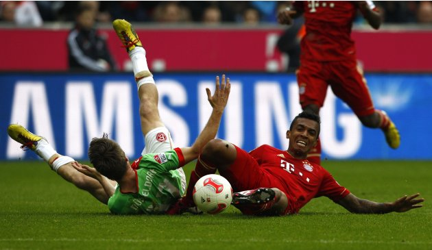 Bayern Munich's Gustavo challenges Duesseldorf's Lambertz during German first division soccer match in Munich