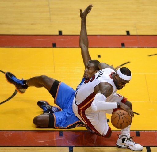 LeBron James (R) of the Miami Heat collides with Serge Ibaka (L) of the Oklahoma City Thunder during Game 3