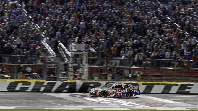 Kevin Harvick takes the checkered flag to win the NASCAR Sprint Cup series Coca-Cola 600 auto race at Charlotte Motor Speedway in Concord, N.C., Sunday, May 26, 2013. (AP Photo/Chuck Burton)