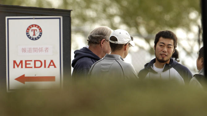 Texas Rangers pitcher Koji Uehara, right, from Japan, talks to the media at baseball spring training on Sunday, Feb. 19, 2012, in Surprise, Ariz. (AP Photo/Charlie Riedel)