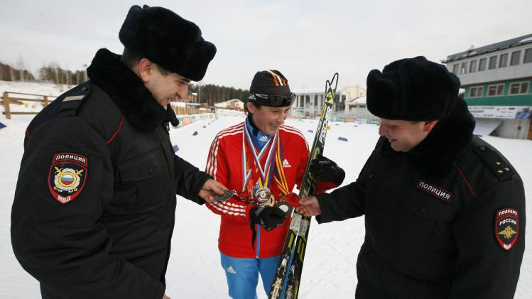 Special task force police officer Irina Samit smiles as her colleagues inspect her medals on the suburbs of Russia's Siberian city of Krasnoyarsk