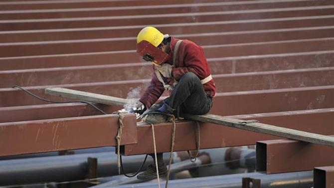 A worker welds the steel frame of a railway station under construction in Hefei, Anhui province December 22, 2013. REUTERS/Stringer