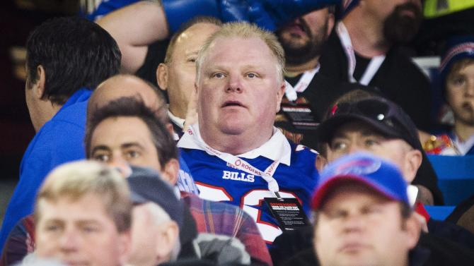 """In this Sunday, Dec. 1, 2013 photo, Toronto Mayor Rob Ford watches the Buffalo Bills play the Atlanta Falcons during the first half of an NFL football game, in Toronto. Saying he's a big Washington Redskins fan and will """"go on any radio,"""" scandal-plagued Ford has agreed to appear on a Washington-based sports talk show to make NFL picks. (AP Photo/The Canadian Press, Mark Blinch)"""